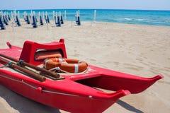 Спасательная лодка с lifebuoy на береге против пляжа и моря Стоковые Изображения