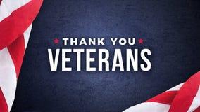 Спасибо текст ветеранов с американскими флагами над синей предпосылкой Стоковое Изображение