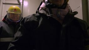 Спасители женщин в защитных костюмах и шлемы идя в тоннель с электрофонарем руки пока спасающ людей внутрь акции видеоматериалы