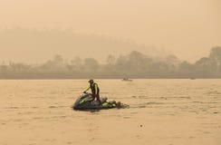 Спаситель воды на jetski с самосхватом 2 sporters в кормовой плавать Стоковое Изображение