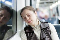 Спать девушка сидя в поезде Стоковые Изображения