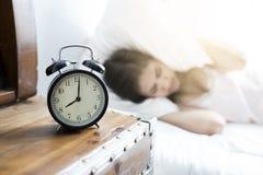 Спать женщина и будильник Азии просыпают вверх Стоковая Фотография
