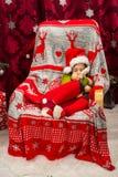 Спать мальчик в плюше игрушки северного оленя удерживания стула стоковые фото