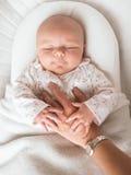 спать родителя s удерживания руки младенца Стоковое Изображение