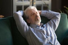 Спать серый с волосами человек ослабляя на удобной софе дома стоковое фото