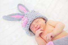 Спать усмехаясь newborn младенец как кролик Стоковые Изображения