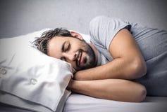 Спать человек в кровать Стоковые Изображения