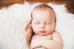 Спать newborn младенец в обруче на белом одеяле Стоковые Фото