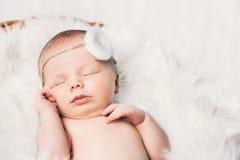 Спать newborn младенец в обруче на белом одеяле Стоковая Фотография