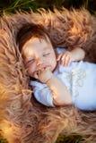 Спать shaggy ребёнок всасывая его руку, конец-вверх, лето Стоковая Фотография RF