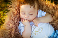Спать shaggy ребёнок всасывая его руку, конец-вверх, лето Стоковые Изображения RF