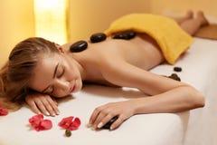 спа 7 Красивая блондинка получает каменный массаж Здоровье Co стоковая фотография