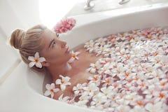 Спа ослабляет Белокурая наслаждаясь ванна с цветками plumeria тропическими r Девушка крупного плана красивая сексуальная купая с  стоковые фотографии rf
