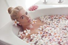 Спа ослабляет Белокурая наслаждаясь ванна с цветками plumeria тропическими r Девушка крупного плана красивая сексуальная купая с  стоковое изображение rf
