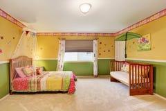 Спальня детей в желтых и зеленых тонах с полом ковра Стоковая Фотография