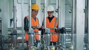 2 специалиста по фабрики регулируют оборудование заваривать видеоматериал