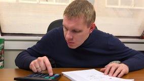 Специалист выполняет вычисление на калькуляторе согласно чертежу сток-видео