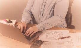 Специалист в ее деле Женщина делая некоторые примечания в тетради и смотря диаграммы на ее рабочем месте стоковая фотография rf