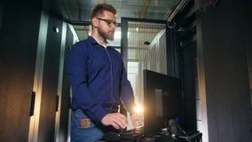 Специалист по ИТ, техник работает компьютер в блоке сервера акции видеоматериалы