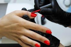 Специалист по маникюра в черных заботах перчаток о ногтях рук Manicurist красит ногти с красным маникюром стоковые изображения