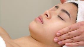 Специалист по массажа гладит рукой лоб ` s девушки стоковая фотография