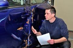 Специалист страхования работая на поврежденном автомобиле стоковые фото