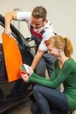 Специалист по автомобиля клеймя советует с клиентом о слипчивых фольгах или фильмах для автоматический оборачивать Стоковая Фотография