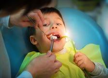 Специалист по мальчика посещая в зубоврачебной клинике стоковая фотография