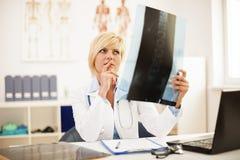 Специалист проверяя рентгеновский снимок Стоковые Изображения