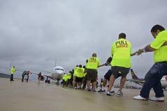Специальные Олимпиады объединяются в команду самолет тяг объединенный на ненастном Чикаго O& x27; Международный аэропорт зайцев Стоковые Фотографии RF