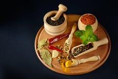 Специи и арахисы разнообразия в деревянных ложках и чашках на черном ба Стоковая Фотография