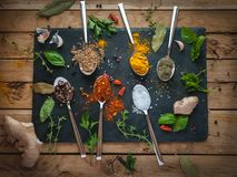 Специи и травы в ложках темной предпосылке, взгляд сверху стоковое фото
