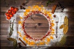Специи на деревянном столе с силуэтом столового прибора Стоковые Изображения RF
