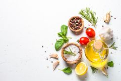 Специи, травы и оливковое масло над белой каменной таблицей Стоковое Изображение