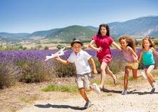 Спешность 3 девушек после самолета игрушки удерживания мальчика Стоковые Изображения