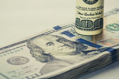 Спиральная долларовая банкнота 100 которая отдыхает на других двинула под углом долларовая банкнота 100 изолированная на белой пр Стоковые Изображения RF