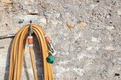 Спиральная смертная казнь через повешение шланга сада на faucet против каменной стены Стоковые Фотографии RF