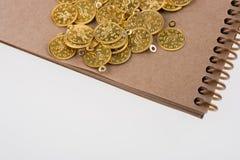 Спиральная тетрадь и золотые монетки Стоковая Фотография RF