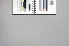 Спиральная тетрадь и различные чертегные инструменты на сером цвете рециркулировали бумагу Стоковая Фотография RF