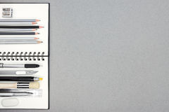 Спиральная тетрадь и различные чертегные инструменты на сером цвете рециркулировали бумагу Стоковое Фото