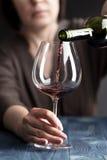Спиртная женщина льет вино в стекло на кухне Стоковое Изображение RF
