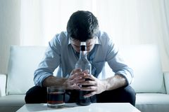 Спиртной бизнесмен нося голубую свободную связь пьяную с бутылкой вискиа на кресле Стоковая Фотография RF