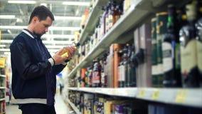 Спиртной esthete среднего возраста выбирает духи на шкафе в торговом центре видеоматериал