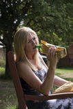 Спирт женщины выпивая от стеклянной бутылки в бумажной сумке Стоковая Фотография