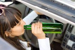 Спирт женщины выпивая пока управляющ автомобилем Стоковая Фотография