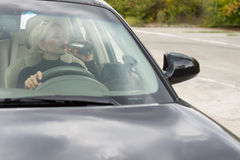 Спирт женщины выпивая пока управляющ автомобилем Стоковое Фото