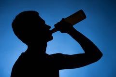 Спирт молодого человека выпивая от бутылки. Стоковые Изображения