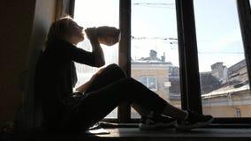 Спирт питья девушки, сидя дальше на windowsill Конец-вверх Стоковые Фото