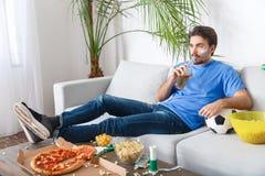 Спичка болельщика молодого человека наблюдая в голубой футболке держа бутылку пива Стоковое Фото
