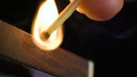 Спичка двигает на сторону matchbox и освещает вверх Конец-вверх поле глубины отмелое движение медленное видеоматериал
